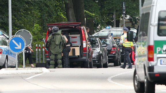 Policemen stand in the area where a gunman had taken people hostage on July 4, 2012.
