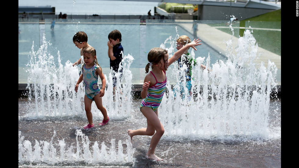 Chilren play in the fountain away form Thursday's scorching temperatires at the Yards Park.