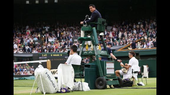 Umpire James Keothavong looks on as Novak Djokovic of Serbia and Roger Federer of Switzerland take a break during their Gentlemen