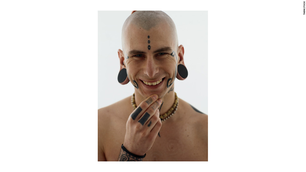 A man displays tattoos, earplugs and a conch piercing.