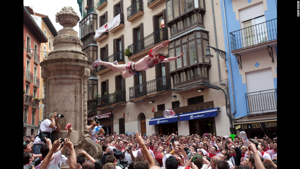 A reveler jumps from a fountain into the crowd at Plaza de Navarreria during the Chupinazo.
