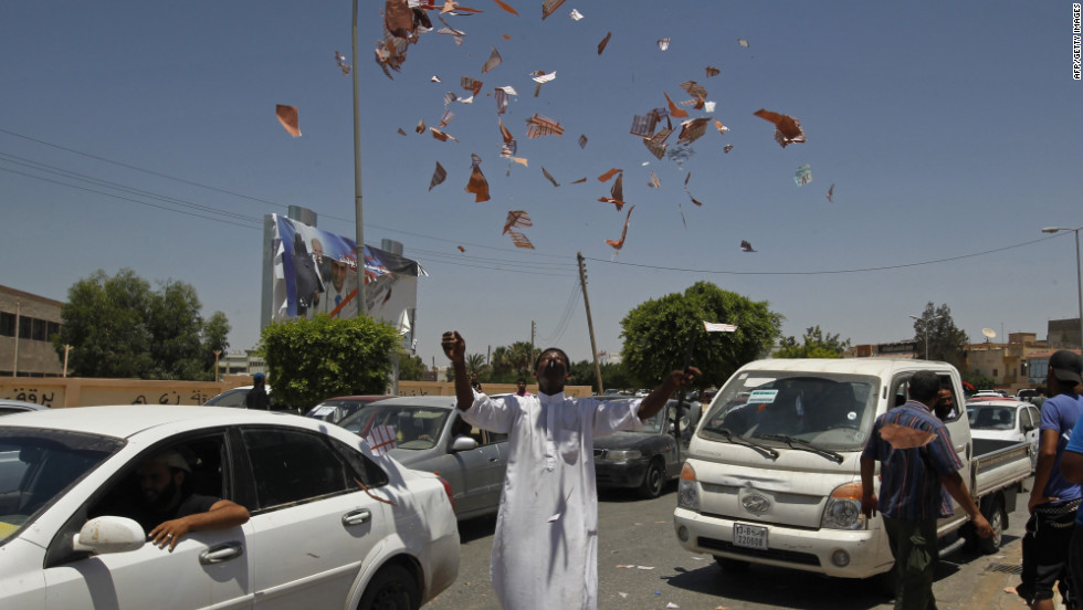 A Libyan protester throws torn ballots in the air outside a Benghazi polling station.