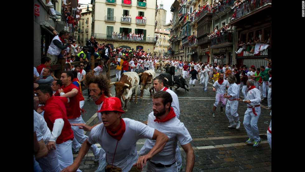 Participants run out of the way of Dolores Aguirre fighting bulls before entering the Estafeta corner.