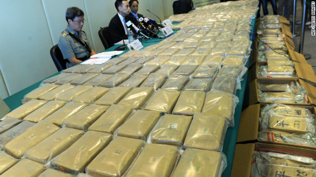 A customs officer stands besides seized cocaine packages during a press conference in Hong Kong on July 6, 2012.