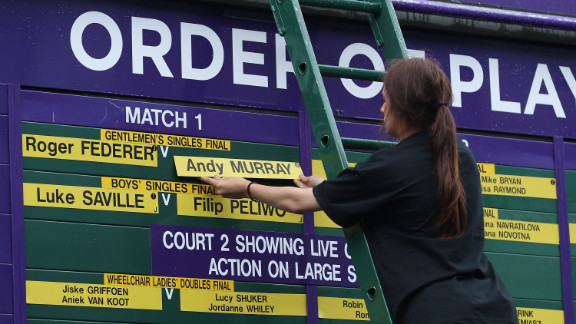 An official changes the order of play board at the All England Lawn Tennis Club ahead of the championship match Sunday.