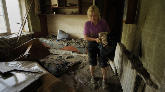 A resident of Krymsk inspects her home, damaged by the flooding that followed heavy rains that began Friday, pushing rivers and streams over their banks overnight.