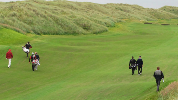 Trump, far left, marches down the fairway for the first time, accompanied by Montgomerie. The American's plans to continue construction have been unpopular with locals.