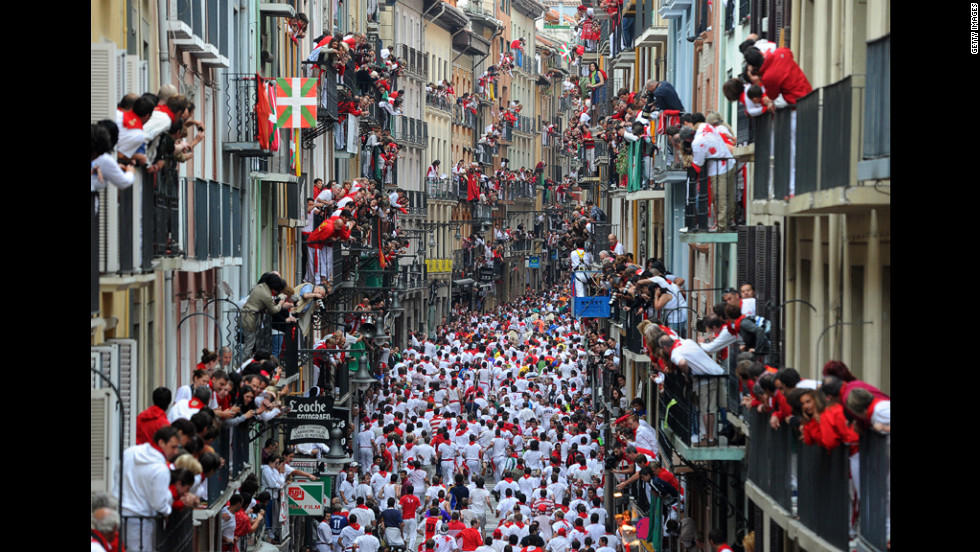 Thousands fill the streets and balconies along Estafeta Street during the San Fermin festivities Monday.