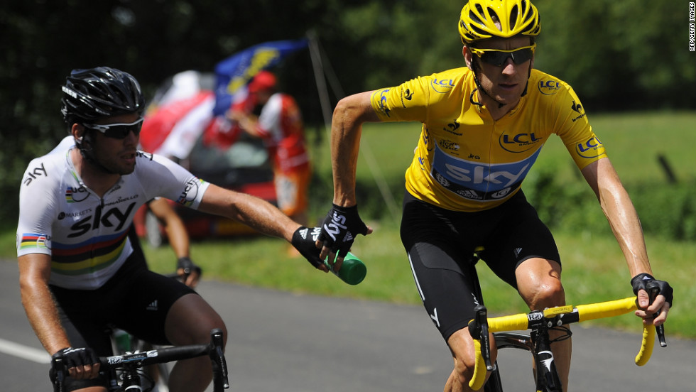 Overall race leader Bradley Wiggins, right, receives a water bottle handoff from Team Sky teammate Mark Cavendish on Wednesday.