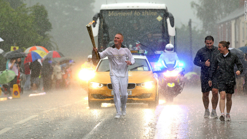 Retired police officer Glenn Chambers carries the flame through heavy rain in Lincoln, England, on June 28.