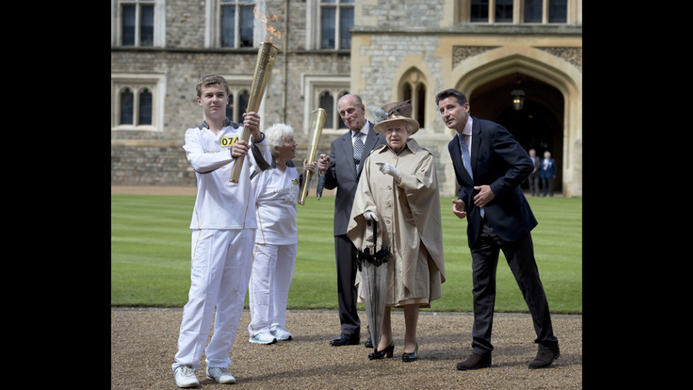 Prince Philip, Queen Elizabeth II and Lord Sebastian Coe watch as Olympic torchbearer Gina Macgregor passes the flame to Phil Wells at Windsor Castle in Windsor, England, on July 10.