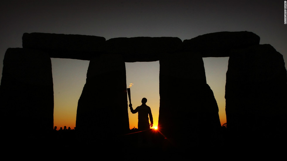 Olympic gold medalist and former sprinter Michael Johnson carries the flame at Stonehenge onThursday.