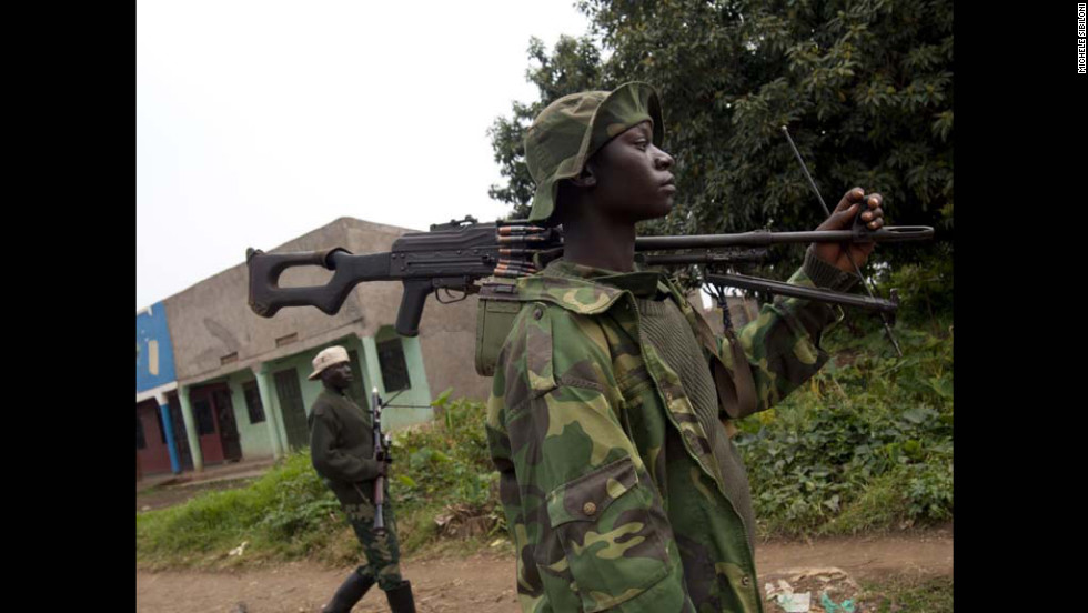 Soldiers from the M23 movement walk in the town of Bunagana. The M23--a group of former Tutsi rebels who had been integrated in the regular army in 2009--has been battling Democratic Republic of Congo troops since May.  The army is known as the FARDC.