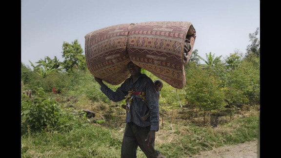 A refugee carries a baby and a bed roll to the Kiwanja refugees camp.