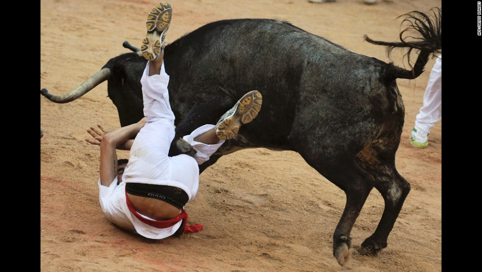 A bull takes down a runner after a San Fermin Festival bull run, on Friday, in Pamplona, northern Spain.