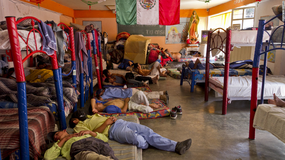 Some nap, while others watch television, at the Casa del Migrante. Residents of the neighborhood have called for the immigrant shelter to close.