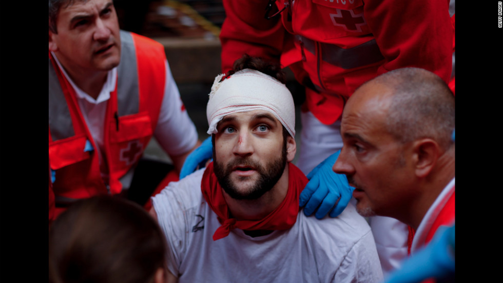 A wounded man is treated for a head injury after running with Torrehandilla Torreherberos fighting bulls on Saturday.