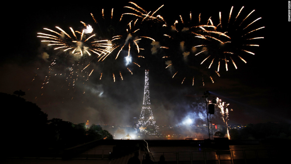People watch as fireworks illuminate the night sky near the Eiffel Tower during the annual Bastille Day celebrations on July 14, 2012 in Paris.