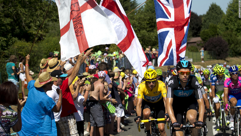 Fans applaud Great Britain's Bradley Wiggins, here in the yellow jersey, as he makes his way up a climb in the main group Monday.