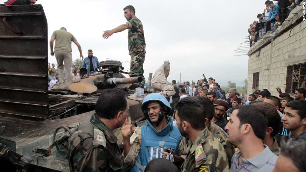 A U.N. observer speaks with Syrian rebels and civilians in the village of Azzara on May 4, 2012, days before the country's parlianemtary polls were held against a backdrop of unrest.