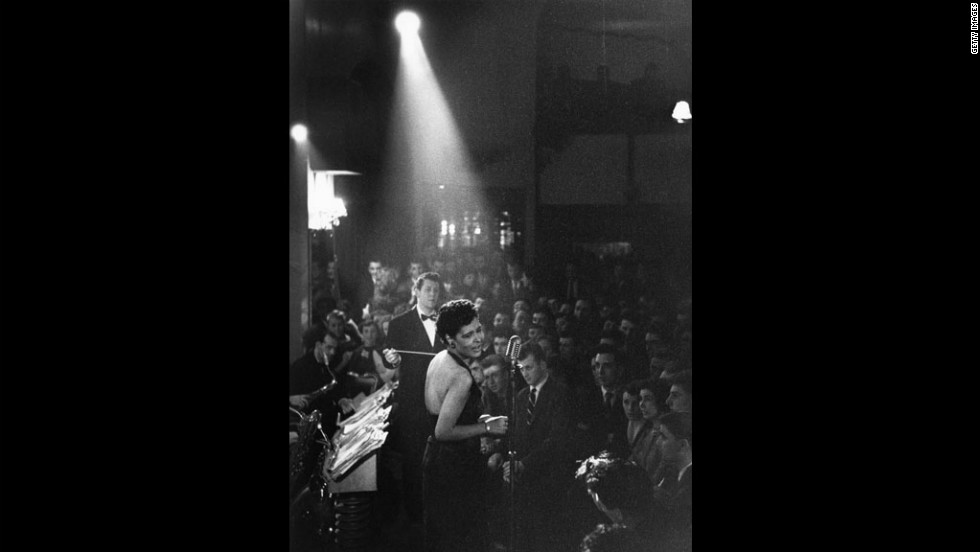 Holiday performs under a spotlight at a club in 1954.