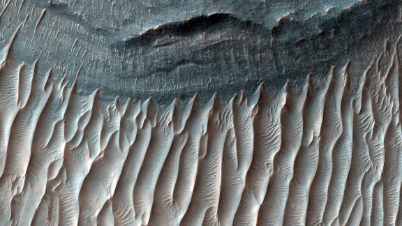 This 2008 image spans the floor of Ius Chasma's southern trench in the western region of Valles Marineris, the solar system's largest canyon. Ius Chasma is believed to have been shaped by a process called sapping, in which water seeped from the layers of the cliffs and evaporated before it reached the canyon floor.