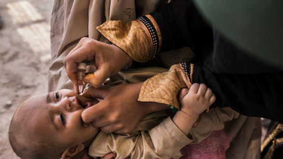 A three-month-old infant receives polio vaccination drops from his mother at a camp in Jalozai, Pakistan on July 13.