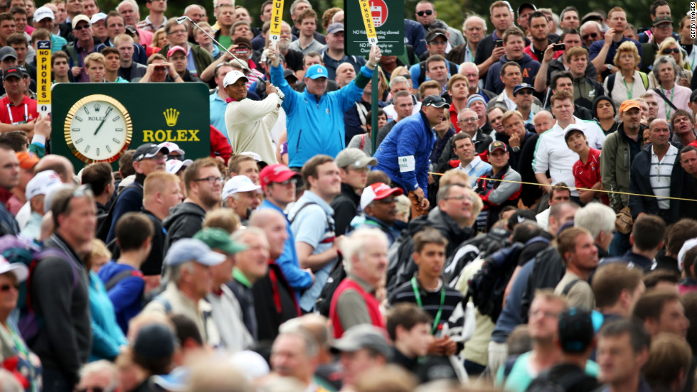 Amid a sea of spectators, Woods plays a shot to the green on the 14th hole Thursday.