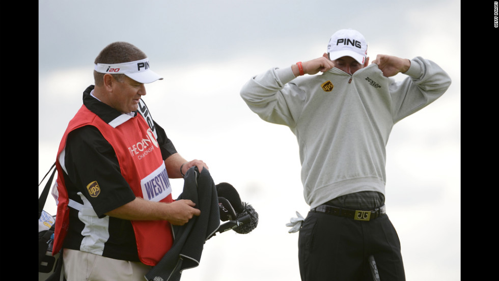With caddie Michael Waite at his side, Lee Westwood of England removes his jacket during the first round Thursday.