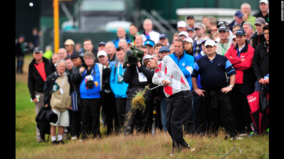 Adam Scott of Australia plays out of the rough on the second hole Thursday under the watchful eyes of spectators.