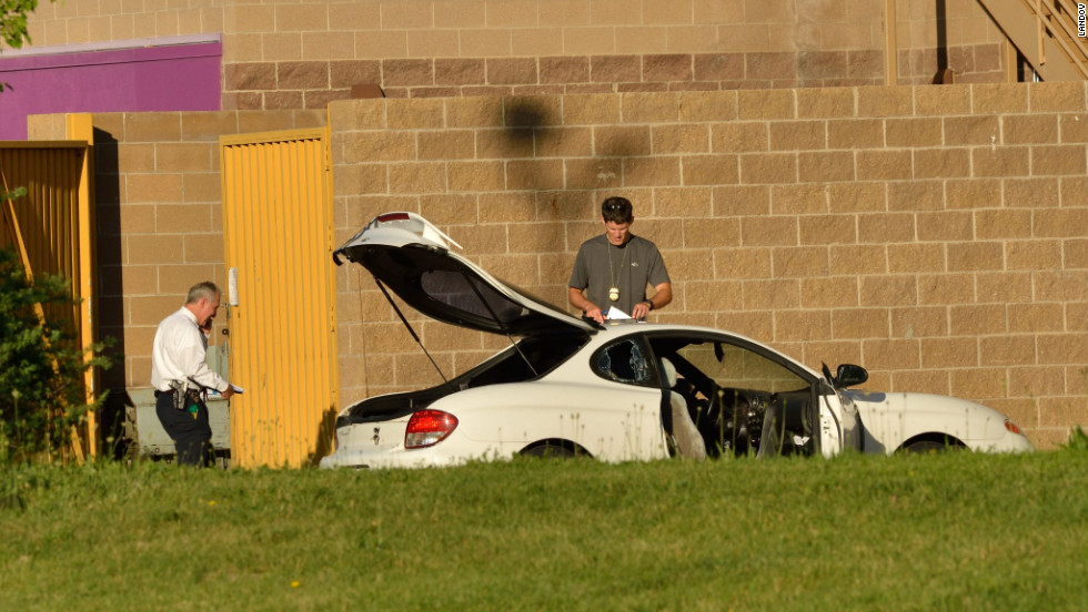 Agents search the suspect's car outside the theater.