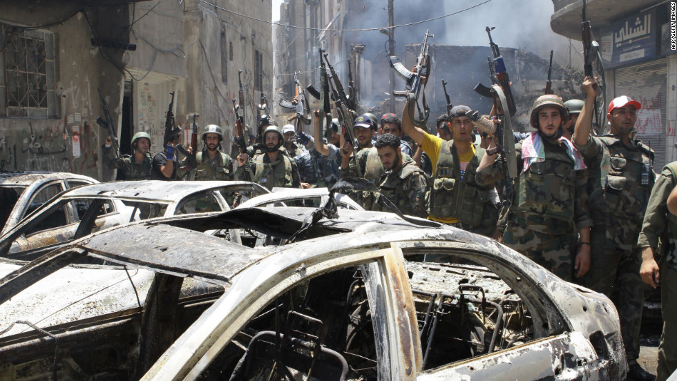 "Syrian soldiers celebrate in the al-Midan area in Damascus on Friday. Syrian regime forces routed rebel fighters from the Damascus neighbourhood of Midan, Syrian state television reported, saying troops had ""cleaned"" the district of ""terrorists."""