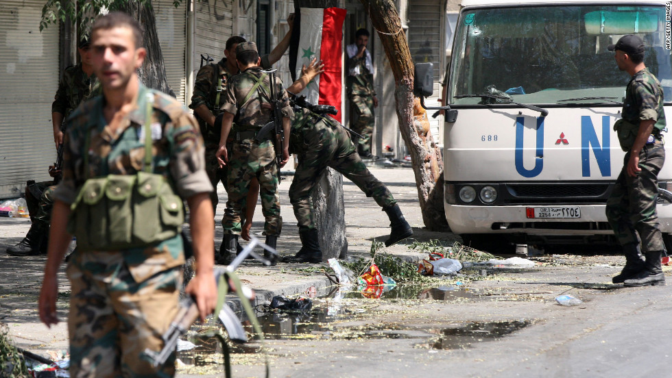 Syrian army soldiers hang their national flag in a partially destroyed neighborhood in the al-Midan area in Damascus.