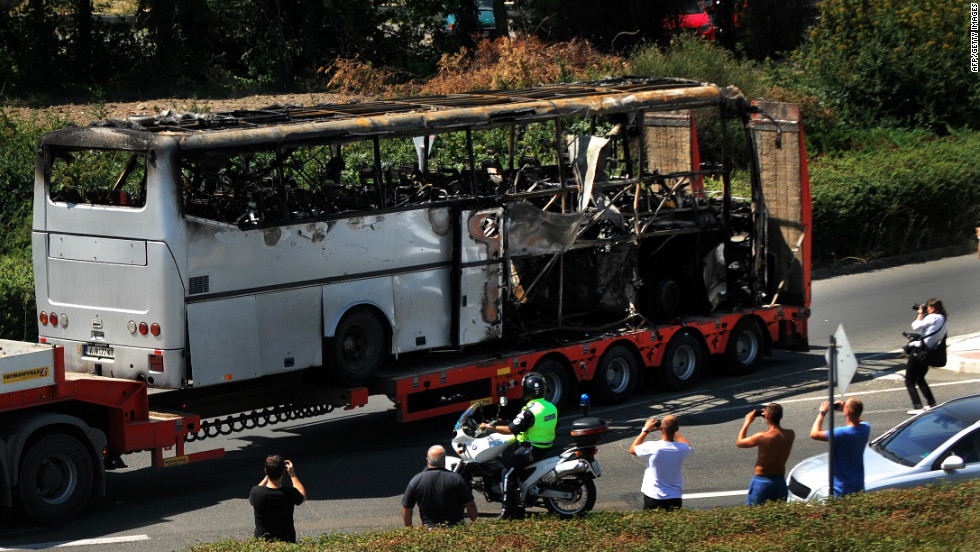 A truck carries the bus damaged by the suicide bomb blast which targeted a group of Israeli tourists in Bulgaria, on Thursday. The suicide bomber was dressed as a tourist carrying fake U.S. ID. Investigators are still trying to find out his identity.
