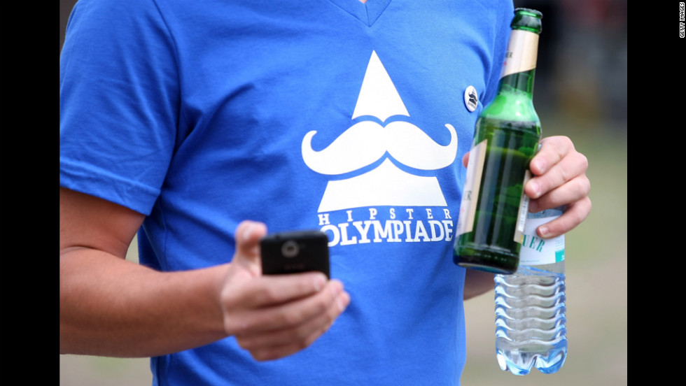 "An attendant wearing a ""Hipster Olympiade"" T-shirt checks his phone."