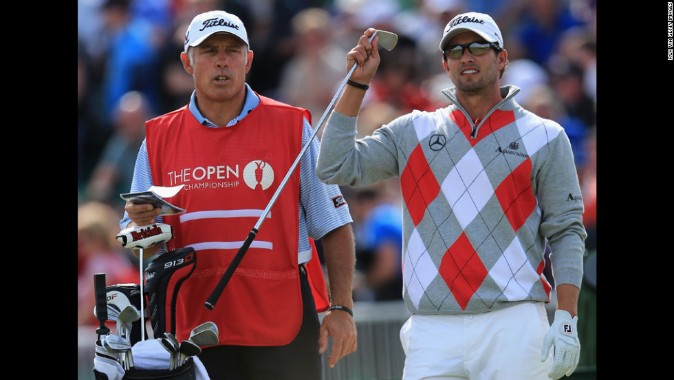 Scott pulls a club as caddie Steve Williams looks on.