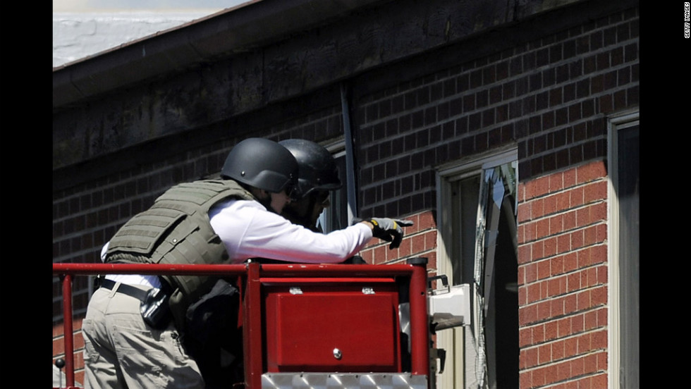 Law enforcement officers prepare to disarm the booby-trapped apartment July 21, 2012.