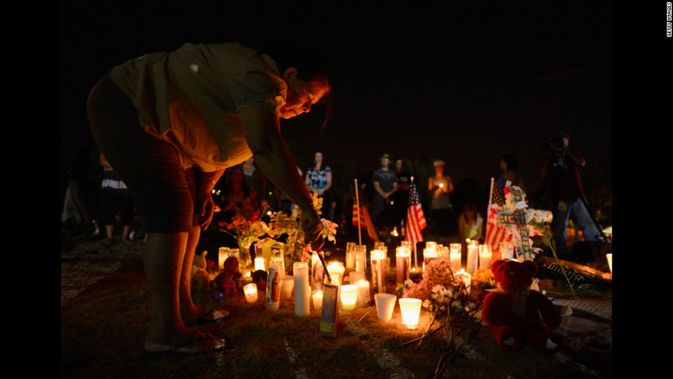 A woman lights a candle at a makeshift memorial where the victims of the massacre are mourned.