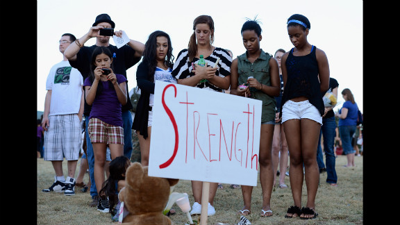 """A group of teenagers stand behind a sign that reads """"Strength."""""""