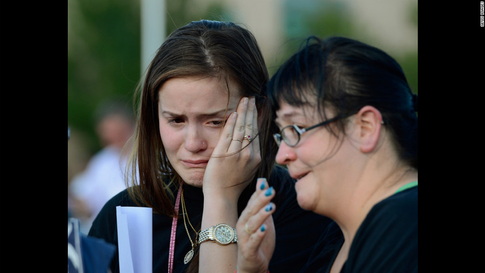 Dara Anderson, left, and Monique Anderson cry during a candlelight vigil across the street from the crime scene.