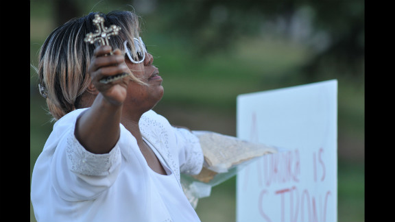 Marietta Perkins of Denver prays for victims and their families.