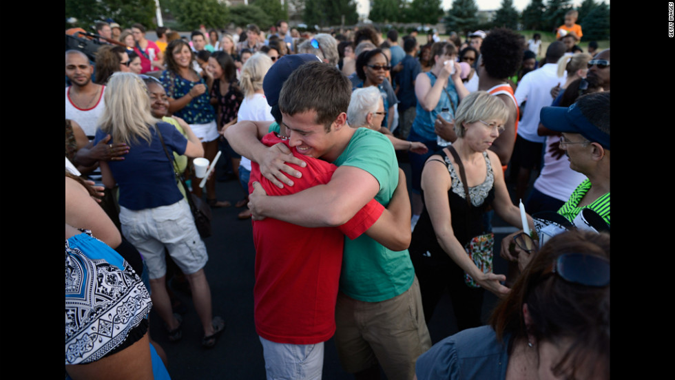 People hug during a vigil for the victims.