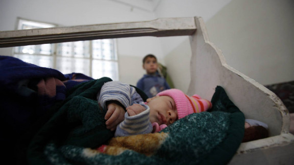 Haldar sits behind his baby brother Hamza at home in al-Ramtha after they fled with his family from Daraa, Syria, in March.