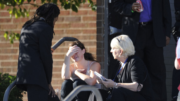 A distraught woman receives counseling from the Rev. Quincy Shannon, left, in front of Gateway High School in Aurora, where the families of the missing met after the shooting.