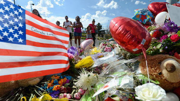 Tiffany Garcia, right, and her 6-year-old daughter, Angelina Garcia, cry on Saturday, July 21, as they look at a memorial for the victims of Friday