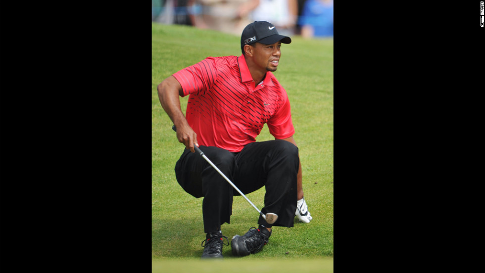 Tiger Woods stumbles and watches the path of his bunker shot on the sixth hole Sunday.