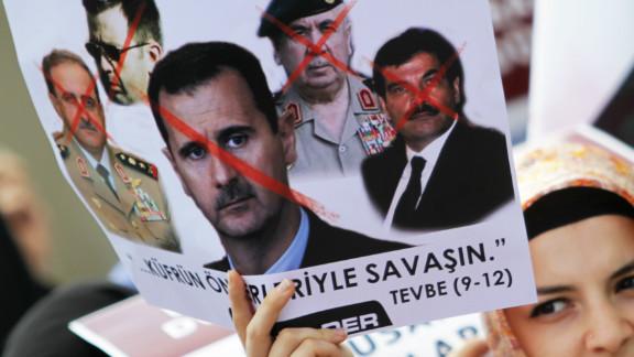 A woman holding a placard protesting against President Bashar al-Assad's regime.