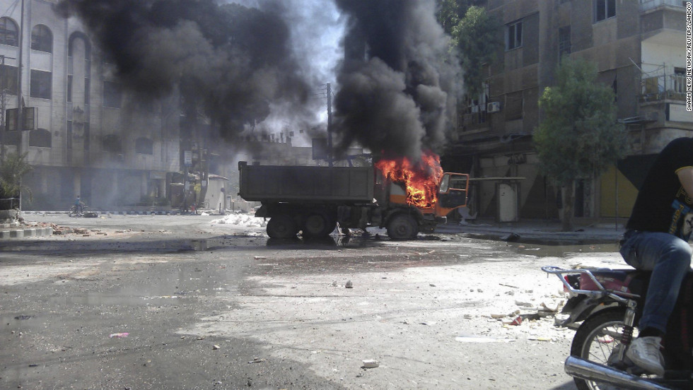 In this photo released by the Shaam News Network, a truck burns after shelling in the Erbeen suburb of Damascus on Saturday, July 21.