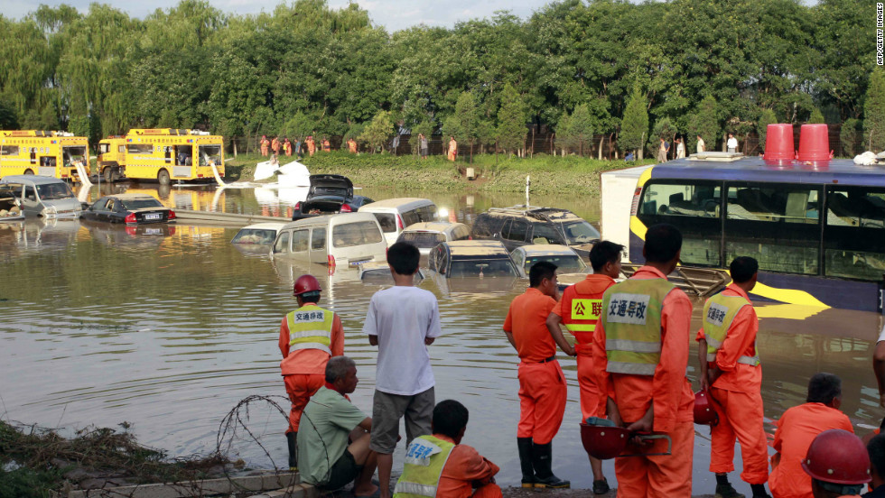 Emergency services personnel try to retrieve damaged vehicles submerged in a flooded carpark after a storm hit Beijing, July 22.