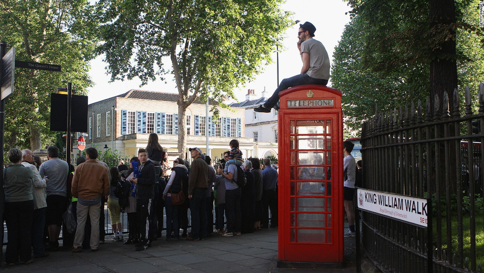 A spectator sits atop a phone booth as people gather to watch the Olympic torch pass through Greenwich in London on Saturday, July 21.